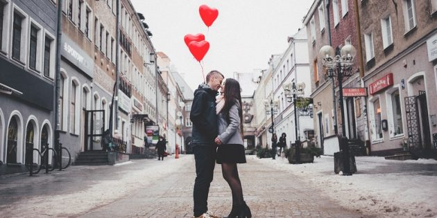 relationship material couple kissing in street with heart balloons
